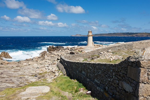 Blick auf einen leuchtturm in der nähe des ozeans mit blauem himmel und weißen wolken Premium Fotos