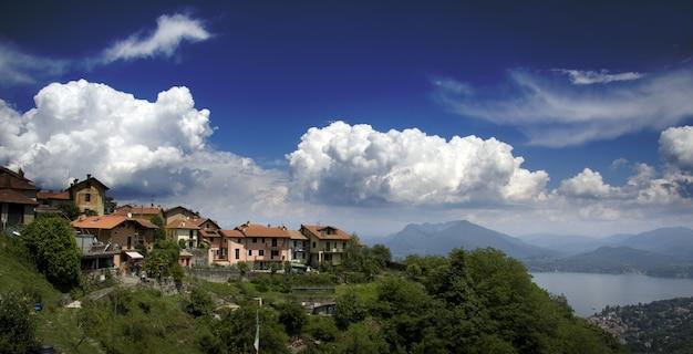 Blick auf häuser auf einem berg mit blick auf ein von bergen umgebenes meer Kostenlose Fotos
