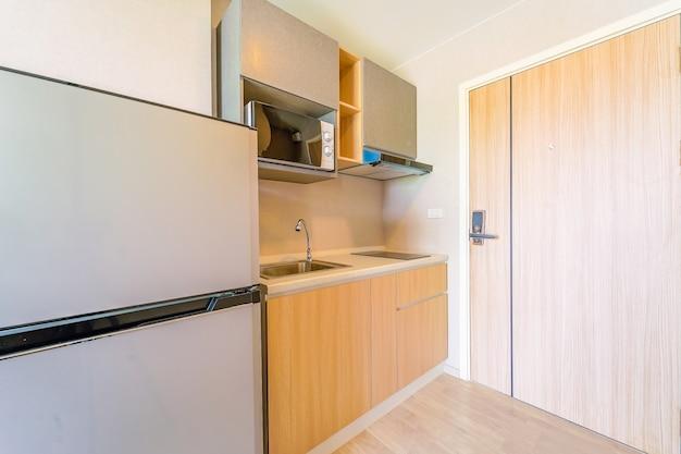 Blick in eine kleine leere küche mit herd, kühlschrank und schränken Premium Fotos