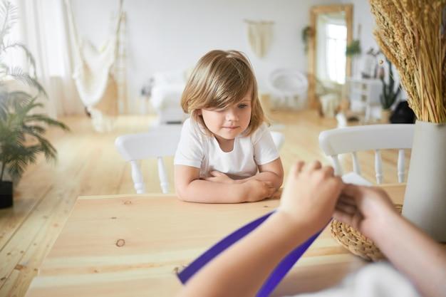 Blick von hinten auf nicht erkennbare kinderhände mit violettem blatt papier. innenaufnahme des niedlichen kleinen mädchens im weißen t-shirt, das am schreibtisch sitzt und beobachtet, wie ihr älterer bruder origami macht. selektiver fokus Kostenlose Fotos