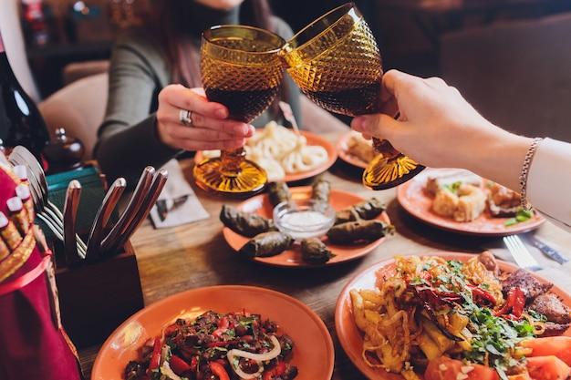 Blick von oben auf die georgische küche auf braunem holztisch. traditionelles georgisches essen - khinkali, kharcho, chahokhbili, phali, lobio und lokale saucen - tkemali, satsebeli, adzhika. draufsicht. kopierraum für text Premium Fotos
