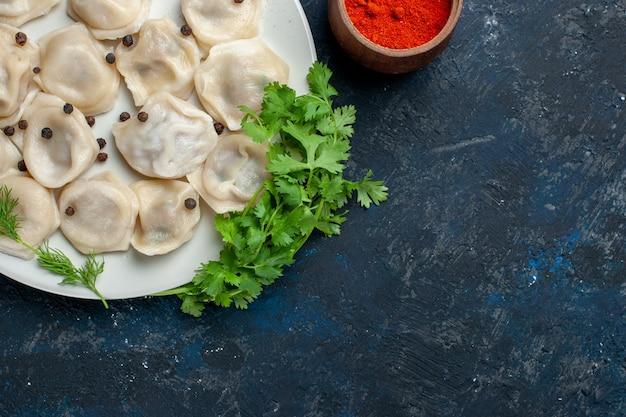 Blick von oben auf köstliche gebackene knödel in der platte zusammen mit pfeffer und gemüse auf einem dunkelgrauen schreibtisch Kostenlose Fotos