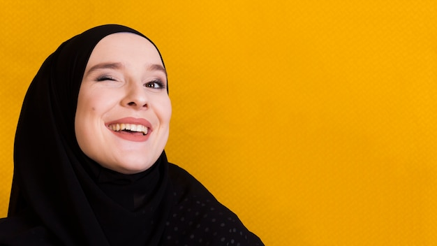 Blinkende augen der glücklichen moslemischen frau über gelbem hintergrund Kostenlose Fotos
