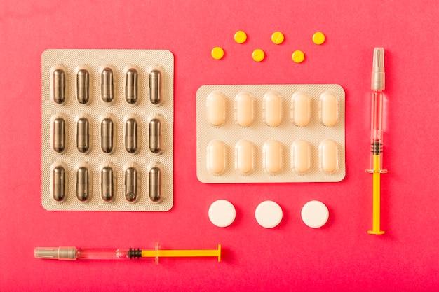 Blisterpackung und -pillen auf rotem hintergrund Kostenlose Fotos