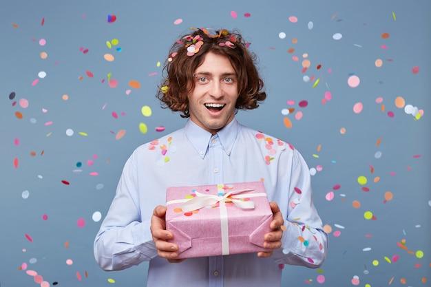Blithesome langhaariger kerl, der geburtstag mit geschenken genießt Kostenlose Fotos