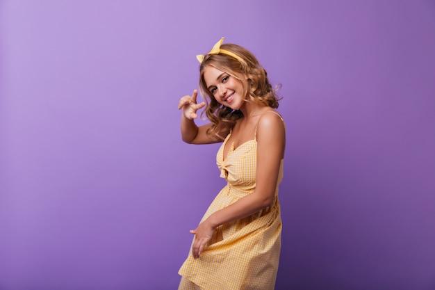 Blithesome mädchen mit bronzehaut lustiges tanzen mit charmantem lächeln. innenporträt der herrlichen kaukasischen frau im gelben outfit. Kostenlose Fotos