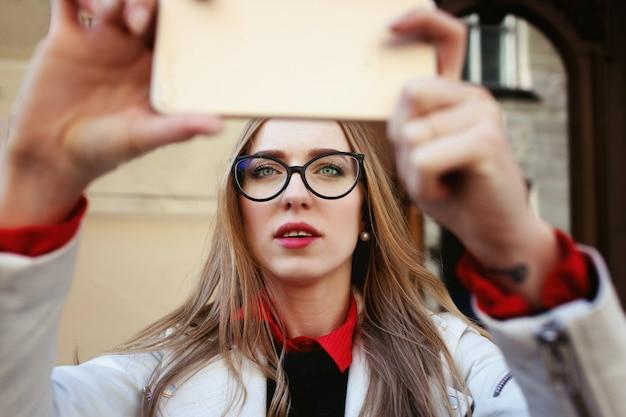 Blnde-mädchen steht mit telefon auf der straße Kostenlose Fotos