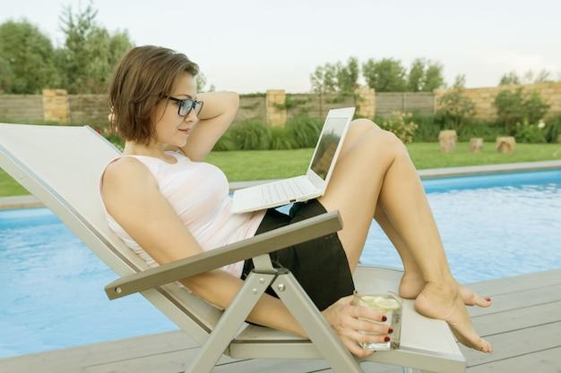 Blogger mit laptop in der nähe des pools Premium Fotos