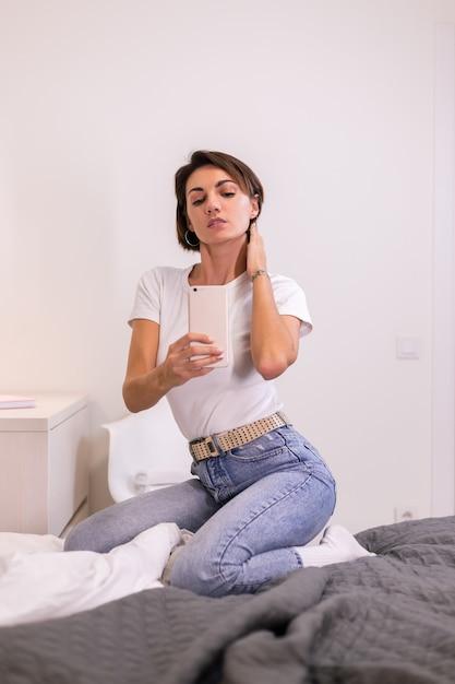 Blogger zu hause in freizeitkleidung gemütliches schlafzimmer macht foto selfie auf handy im spiegel Kostenlose Fotos