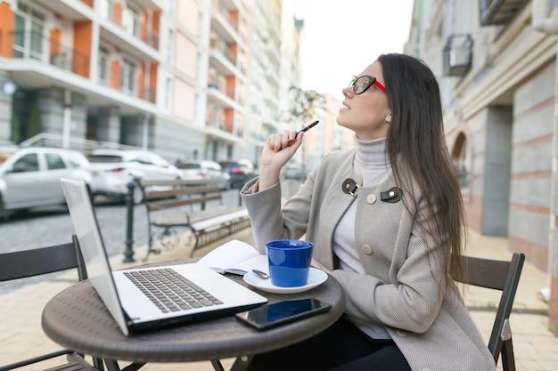 Bloggerin freiberufler im café im freien mit computer Premium Fotos