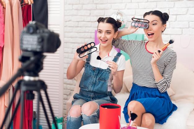 Bloggerinnen halten pinsel und lidschatten hoch. Premium Fotos
