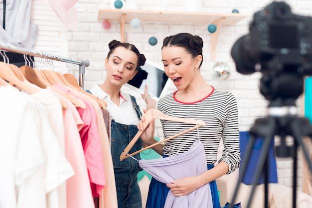 Bloggermädchen präsentieren der kamera ein buntes kleid. Premium Fotos