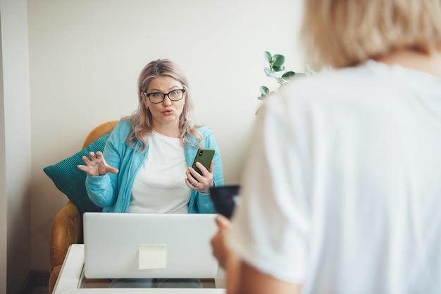 Blonde ältere frau mit brille, die ein telefon hält, erklärt einem kunden etwas, das einen laptop benutzt und zu hause arbeitet Premium Fotos