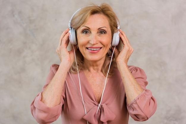 Blonde dame des smiley, die musik auf kopfhörersatz hört Kostenlose Fotos
