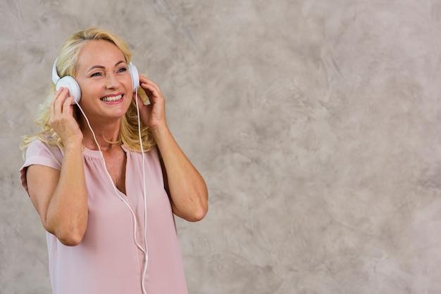 Blonde dame, die musik auf kopfhörersatz hört Kostenlose Fotos
