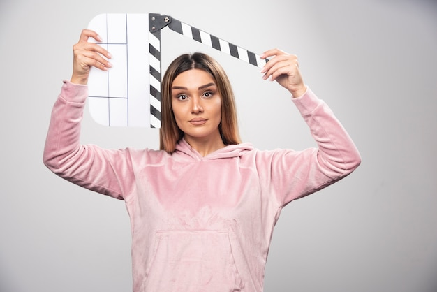 Blonde dame im rosa sweatshier hält eine leere klappe und schaut durch. Kostenlose Fotos