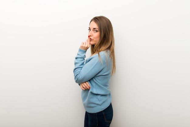 Blonde frau auf dem lokalisierten weißen hintergrund, der ein zeichen des schließens der mund- und ruhegeste zeigt Premium Fotos