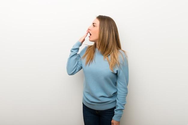 Blonde frau auf lokalisiertem weißem hintergrund, der weit offenen mund mit der hand gähnt und bedeckt Premium Fotos