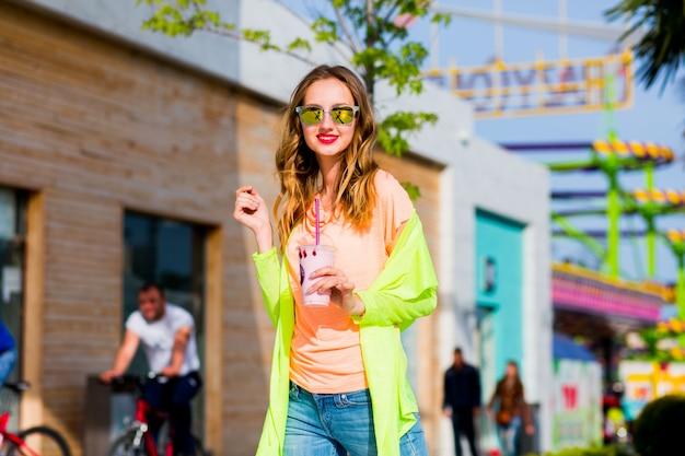 Blonde frau des hipsters in der kühlen sonnenbrille mit cocktail, der draußen aufwirft Kostenlose Fotos