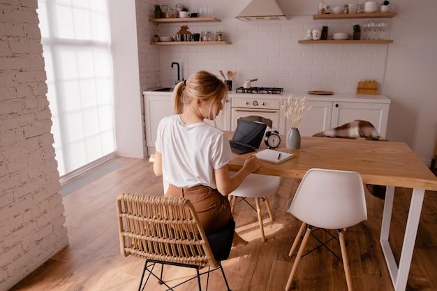 Blonde frau, die am tisch sitzt und ihren hals massiert. Premium Fotos