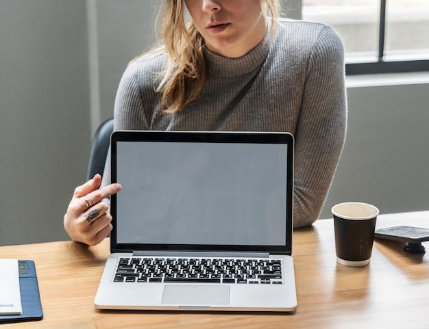 Blonde frau, die auf einen laptopbildschirm zeigt Kostenlose Fotos