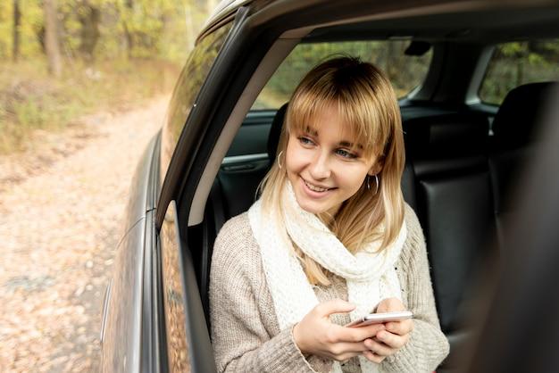 Blonde frau, die ein telefon anhält und weg schaut Kostenlose Fotos
