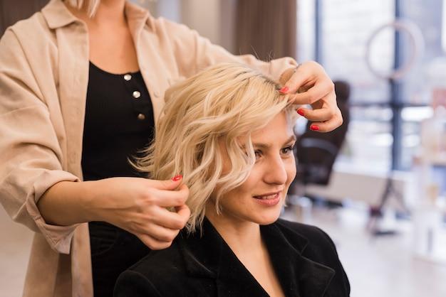 Blonde frau, die ihr haar erledigt bekommt Kostenlose Fotos