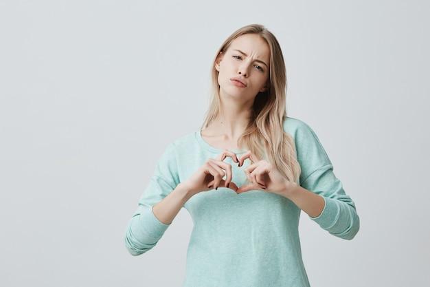 Blonde frau, die liebeszeichen mit ihren händen zeigt, die in herzform hohlen. schöne europäische frau, die lässig gekleidet ist, fühlt liebe. konzept der romantik und der menschlichen beziehungen. Kostenlose Fotos