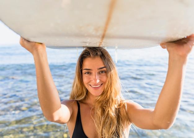 Blonde frau, die surfbrett auf kopf hält Kostenlose Fotos