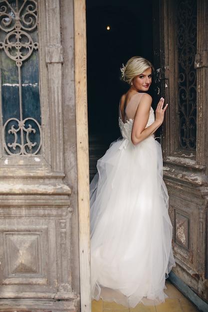Blonde Frau, gekleidet wie eine Braut an einer Tür gelehnt ...