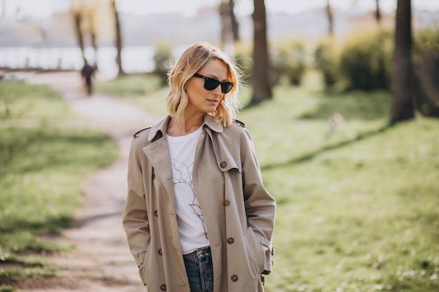 Blonde frau im mantel draußen im park Kostenlose Fotos