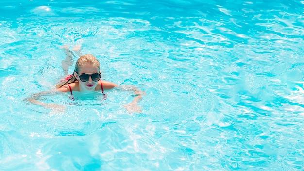 Blonde frau im pool schwimmen | Kostenlose Foto