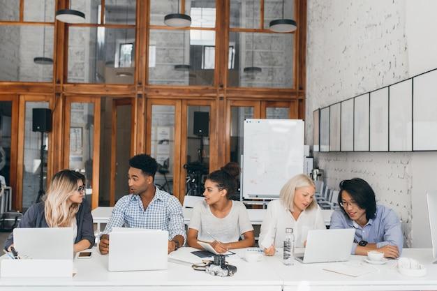 Blonde frau im weißen hemd, das mit asiatischem freund spricht und kaffee nahe laptop mit flipchart trinkt. freiberufliche webdesigner, die im konferenzsaal zusammenarbeiten und computer verwenden. Kostenlose Fotos