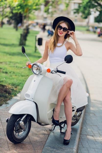 Blonde frau im weißen tüllrock und in den schwarzen absätzen, die auf vintage roller sitzen. Kostenlose Fotos