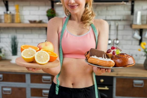Blonde frau in der küche mit früchten Kostenlose Fotos