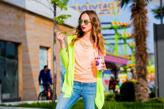 Blonde frau in der kühlen sonnenbrille mit cocktail, der draußen aufwirft Kostenlose Fotos