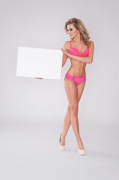 Blonde frau in der sexy unterwäsche, die whiteboard zeigt Kostenlose Fotos