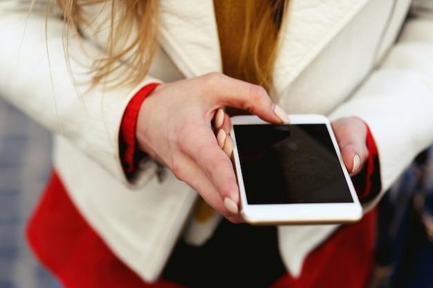 Blonde frau in der weißen jacke macht ein foto an ihrem telefon Kostenlose Fotos