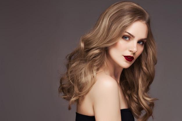 Blonde frau mit dem lockigen schönen haar lächelnd auf grauem hintergrund. Premium Fotos