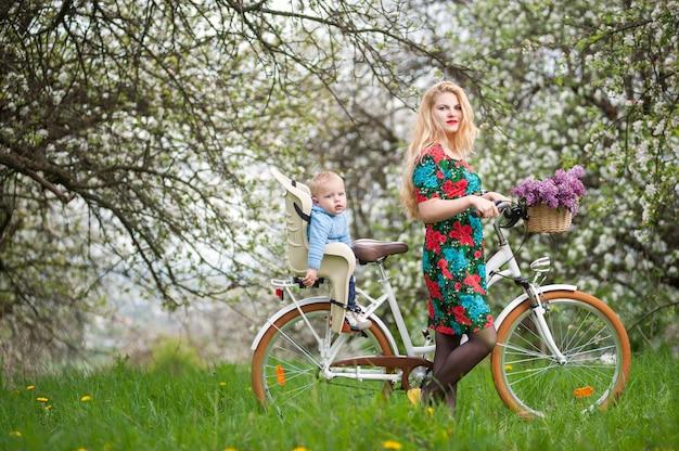 Blonde frau mit stadtfahrrad mit baby im fahrradstuhl Premium Fotos