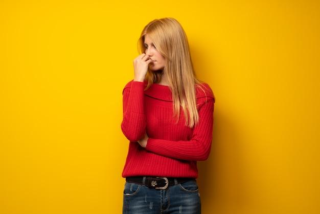 Blonde frau über der gelben wand, die zweifel hat Premium Fotos