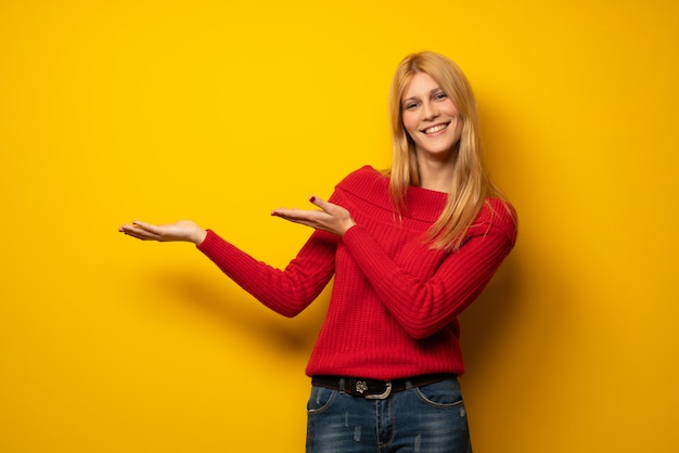 Blonde frau über gelben ausdehnungshänden zur seite für die einladung zu kommen Premium Fotos