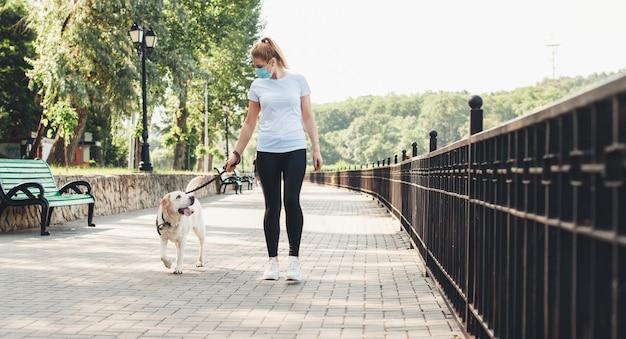 Blonde frau und ihr hund gehen im park, während sie eine medizinische maske auf gesicht während des coronavirus tragen Premium Fotos