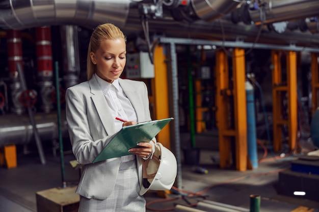 Blonde geschäftsfrau, die im heizwerk steht, zwischenablage hält und maschinen überprüft. Premium Fotos