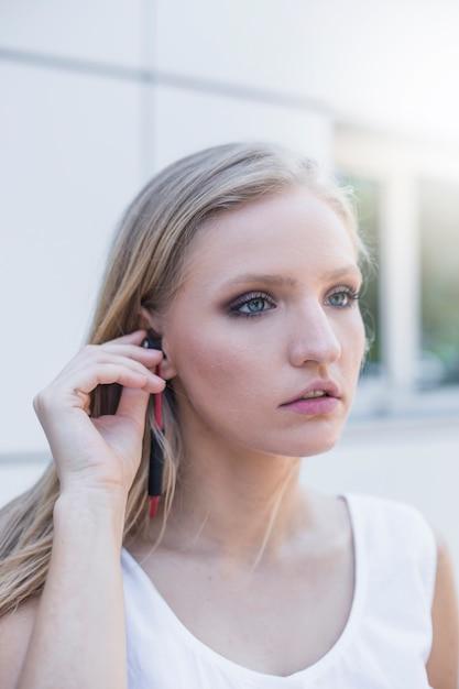 Blonde hörende musik der jungen frau auf kopfhörer Kostenlose Fotos