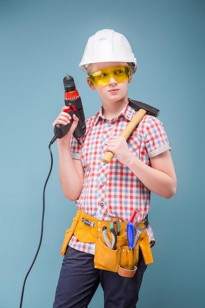 Blonde jugendlichblondine im bausturzhelm mit einem schraubenzieher und einem hammer Premium Fotos