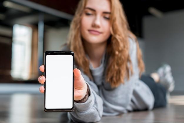 Blonde junge frau, die auf dem boden zeigt handy mit weißer bildschirmanzeige liegt Kostenlose Fotos