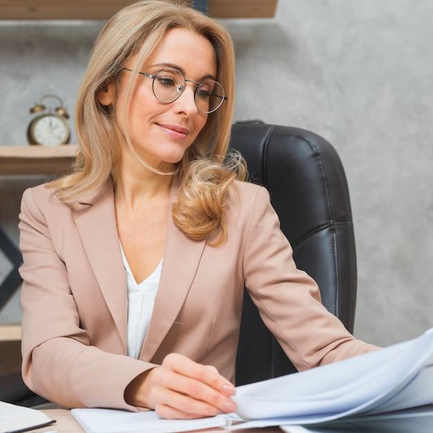 Blonde junge frau, die auf dem stuhl überprüft die geschäftsdokumente am arbeitsplatz sitzt Kostenlose Fotos