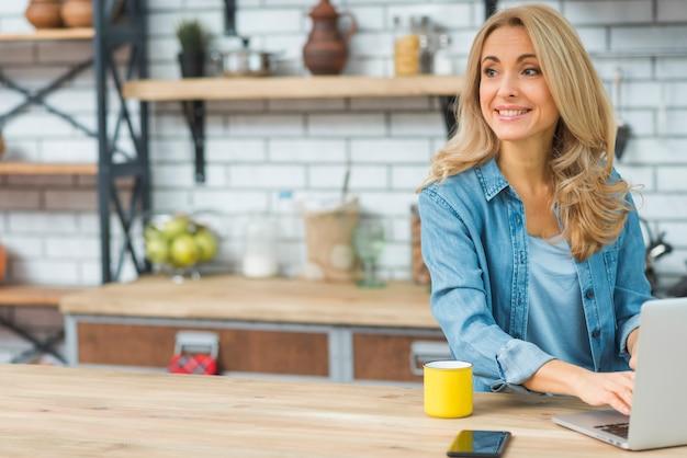 Blonde junge frau, die auf laptop mit kaffeetasse und handy auf tabelle schreibt Kostenlose Fotos