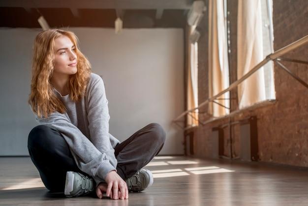 Blonde junge frau, die auf massivholzboden im tanzstudio sitzt Kostenlose Fotos
